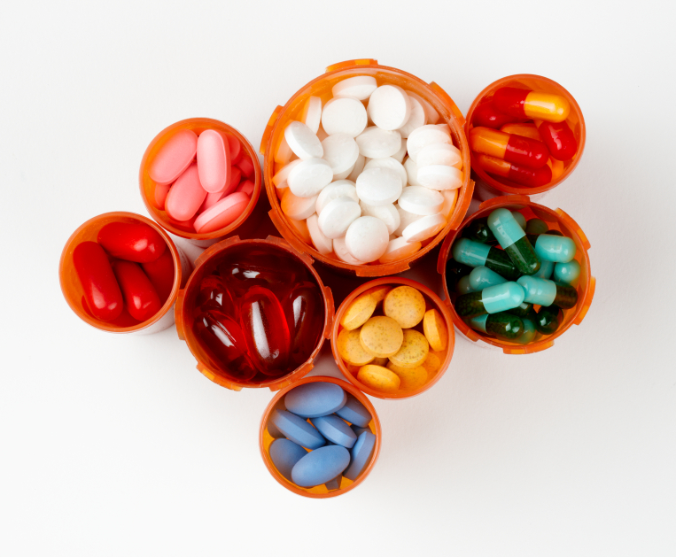 several prescription bottles filled with colorfu pills and capsules, shot from above on white background with soft white drop shadow