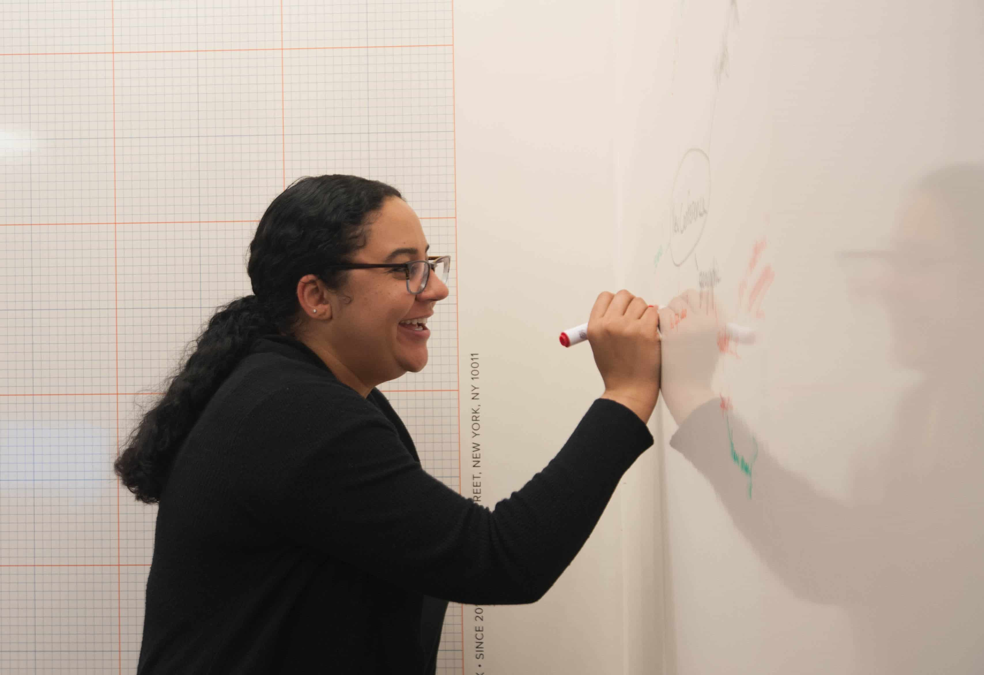 employee writing on whiteboard